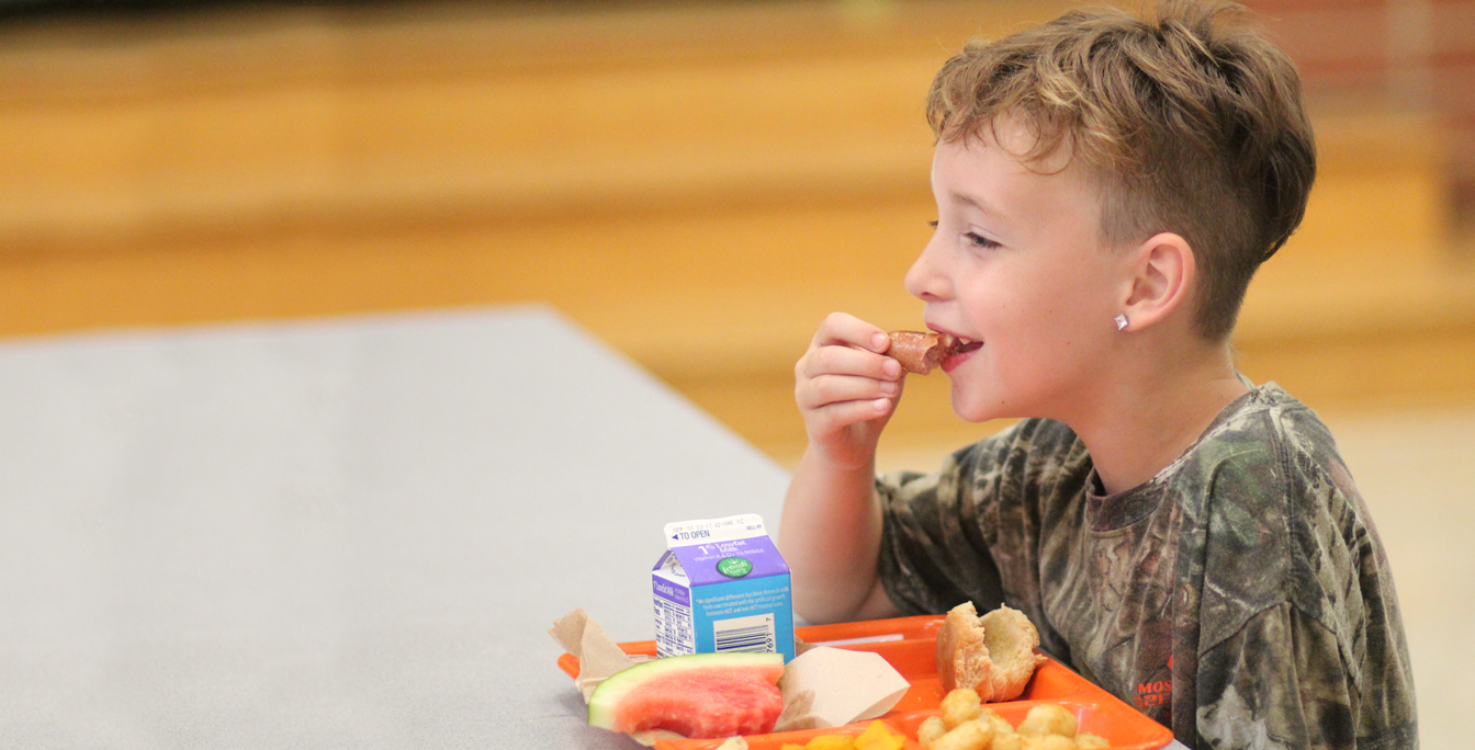 a happy child eating a school lunch