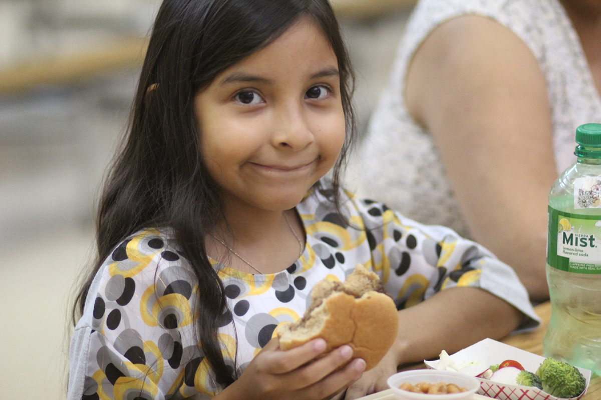 Girl eating a hamburger for lunch.